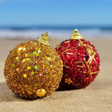 Ornamented christmas balls on the beach. Closeup of some ornamented christmas balls on the sand of a beach, with the sea and the horizon at the background Royalty Free Stock Image