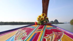 Ornamented and decorated longtail boat drifts along river. Thai longtail boat ornamented with designs and decorated with flowers drifts along river to mountains stock video