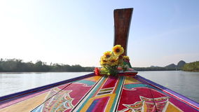 Ornamented and decorated longtail boat drifts along river. Thai longtail boat ornamented with designs and decorated with flowers drifts along river to mountains stock video footage
