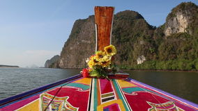 Ornamented and decorated longtail boat sails up to cliffs. Thai longtail boat ornamented with designs and decorated with flowers sails up to cliffs stock video footage