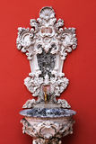 Ornamented faucet on the red wall Royalty Free Stock Photography