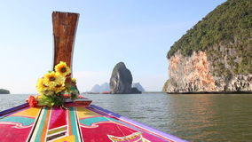 Ornamented longtail boat sails up to village near cliff. Thai longtail boat ornamented with designs and decorated with flowers sails up to fishing village near stock video footage