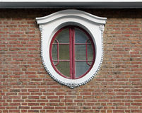 Ornamented oval window brick wall Stock Image