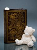 Ornamented wooden casket and teddy-bear on blue Royalty Free Stock Photos