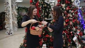 Ornamenti d'acquisto di Natale in negozio Il compratore conta e dà i soldi al venditore e riceve in cambio un canestro stock footage
