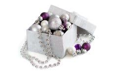 Ornamenti d'argento e porpora di Natale in contenitore di regalo Fotografie Stock