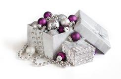 Ornamenti d'argento e porpora di Natale in contenitore di regalo Fotografia Stock