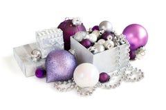 Ornamenti d'argento e porpora di Natale in contenitore di regalo Immagini Stock