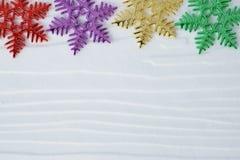 Ornamenti del fiocco della neve su fondo di legno bianco con lo spazio della copia Immagine Stock