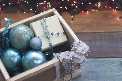 Ornamenti del nuovo anno in una scatola di legno con le luci leggiadramente Immagine Stock Libera da Diritti
