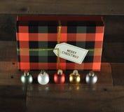 Ornamenti di Natale con il contenitore di regalo del plaid dietro immagine stock libera da diritti