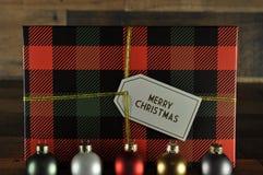 Ornamenti di Natale con il contenitore di regalo del plaid dietro fotografia stock libera da diritti
