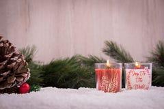 Ornamenti di Natale con neve, il pino, la candela rossa e le luci di natale fotografia stock