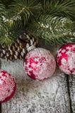 Ornamenti di Natale coperti di neve sulla tavola rustica Fotografia Stock