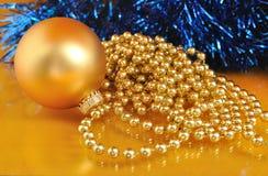 Ornamenti di natale dell'oro sul fondo dell'oro Fotografia Stock