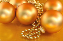 Ornamenti di natale dell'oro sul fondo dell'oro Immagini Stock Libere da Diritti