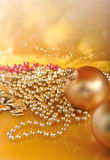 Ornamenti di natale dell'oro sul fondo dell'oro Fotografie Stock Libere da Diritti
