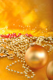 Ornamenti di natale dell'oro sul fondo dell'oro Immagini Stock