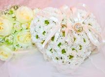 Ornamenti di nozze, anello sul cuscino nella forma di cuore fotografia stock