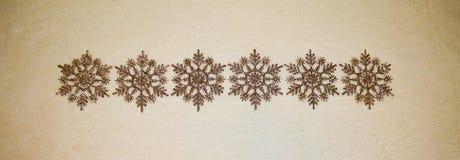 Ornamenti dorati dei fiocchi di neve di scintillio in una fila Fotografia Stock