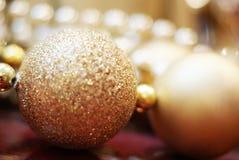 Ornamenti dorati di Natale che brillano Immagine Stock
