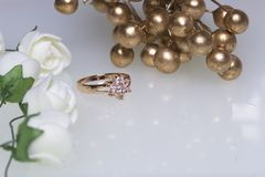 Ornamenti per le celebrazioni Anello di oro con le pietre ed il mazzo dei fiori artificiali Su una priorità bassa bianca Immagini Stock Libere da Diritti