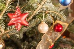 Ornamenti variopinti che appendono sull'albero di Natale Immagini Stock Libere da Diritti