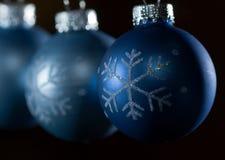 Ornamento azuis do Natal de encontro ao fundo escuro foto de stock