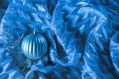 Ornamento blu brillante di Natale sul fondo serico del tessuto prescelto fotografie stock
