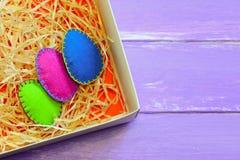 Ornamento coloridos dos ovos da páscoa de feltro Telemóvel amarelo Decoração da casa do feriado da mola Fundo de madeira com luga imagem de stock royalty free
