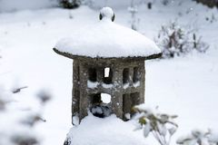 Ornamento concreto asiático de la estatua del jardín cubierto en nieve fotografía de archivo libre de regalías