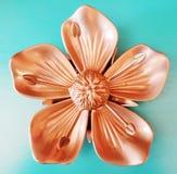 Ornamento de bronce cuadrado de la flor del metal en fondo de la turquesa fotografía de archivo
