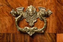 Ornamento de bronze antigo em uma mobília velha do folheado da noz Fotografia de Stock Royalty Free