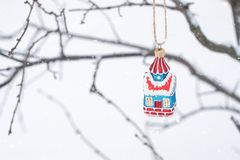 Ornamento de hadas de la casa de la Navidad en árbol de la rama con el fondo blanco como la nieve Fondo con pequeño, espacio del  imagen de archivo