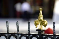 Ornamento de la cerca de la flor de lis del oro en la cerca del hierro labrado Imagenes de archivo