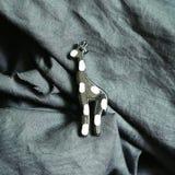 Ornamento de la forma de la jirafa en fondo negro del paño imagenes de archivo