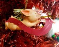 Ornamento de la Navidad del cerdo del vuelo en el árbol de navidad rojo Fotos de archivo libres de regalías