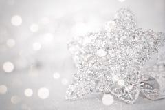 Ornamento de prata brilhantes da estrela no bokeh abstrato brilhante do fundo Foto de Stock