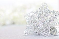 Ornamento de prata brilhantes da estrela no bokeh abstrato brilhante do fundo Fotografia de Stock Royalty Free