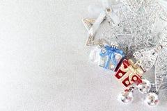 Ornamento de prata vermelhos, azuis e brilhantes no bokeh abstrato brilhante do fundo Fotografia de Stock