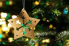 Ornamento decorativo de la estrella del oro en un árbol de navidad Foto de archivo