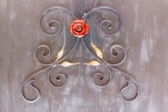 Ornamento decorativo de ramos do metal, de folhas e de uma rosa vermelha sobre imagens de stock