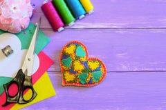 Ornamento del corazón para el día de tarjetas del día de San Valentín El ornamento del corazón del fieltro, hilo, tijeras, fieltr Fotos de archivo libres de regalías