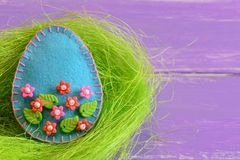 Ornamento del huevo de Pascua con las gotas plásticas coloridas de las flores y de las hojas Ornamento del huevo del fieltro en l Fotos de archivo
