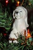 Ornamento del perro de la Navidad en casquillo el dormir con el regalo Imagen de archivo