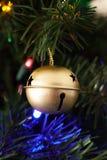 Ornamento di Sleigh Bell dell'oro appeso su un albero di Natale artificiale Fotografie Stock
