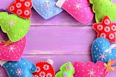 Ornamento diferentes do Natal Árvores de Natal de feltro, mitenes, corações, estrelas no fundo de madeira lilás com espaço vazio  Fotos de Stock