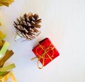 Ornamento do Natal com confetes do ouro, o presente vermelho e o cone do pinho Imagem vertical para o cartão do Natal ou do ano n Imagens de Stock Royalty Free