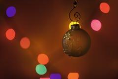 Ornamento do Natal na frente das luzes coloridas Fotografia de Stock