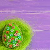 Ornamento do ovo da páscoa de feltro com as flores plásticas coloridas Ornamento do ovo de feltro no ninho e no fundo de madeira  imagem de stock